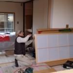 和室では建具屋さんが引き戸取り付け。 組子の間に一枚のアクリル板を入れ、ビスとめと歯車の調整。
