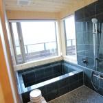洗面脱衣所から左官屋さんが頑張った浴槽。 (なんと窓から桜島が望めます。半露天風呂って感じですよね。) 戸水口は通常の蛇口を付けると一気に雰囲気を壊してしまうと感じた社長が、家具屋さんにお願いをして、壁の一部に使用している高野槇の材料を使ってかっこよく戸水口を制作してもらいました。